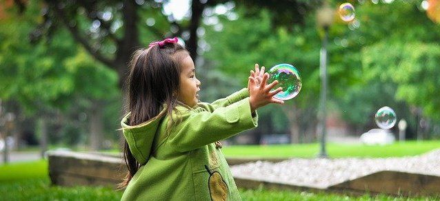 girl chasing bubbles