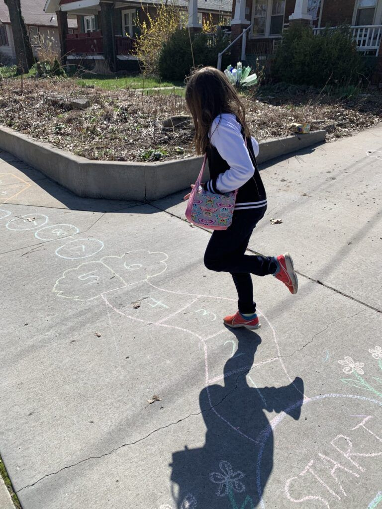 child doing hopskotch drawn with chalk on a sidewalk