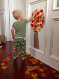 child placing leaves on paper tree