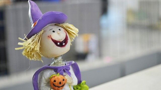 a bobble head witch with a purple hat holding a pumpkin