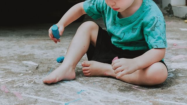 child in blue shirt sitting on the ground holding chalk