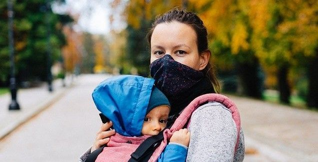 woman standing on path wearing mask holding a child