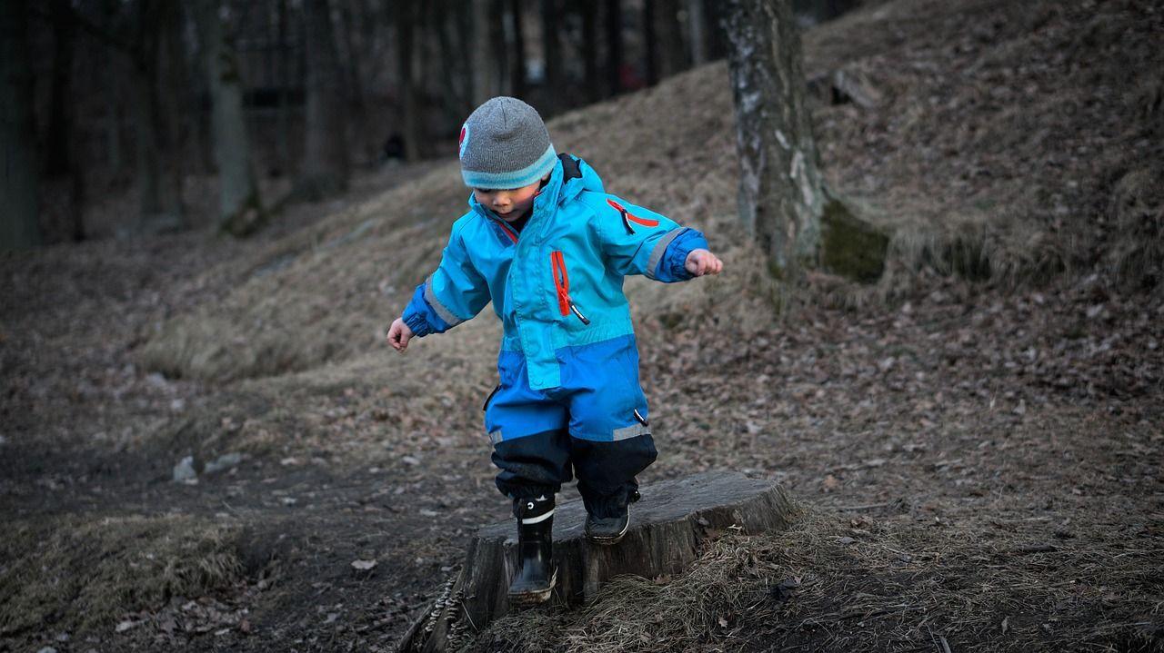 boy balancing on log in blue coat