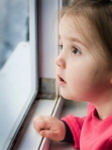 young girl looking out a window looking anxious