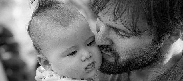 dad kissing baby on cheek