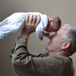 grandfather holding up baby